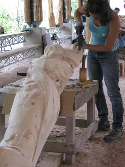 Artiste en train de sculpter du bois au festival Camille Claudel à La Bresse